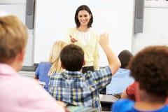 Δάσκαλος που στέκεται μπροστά από την κατηγορία που υποβάλλει την ερώτηση Στοκ Εικόνες