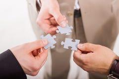 小组装配七巧板的商人。配合。 免版税库存照片