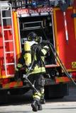有氧气罐火的勇敢的消防队员在举行的锻炼期间 免版税库存图片