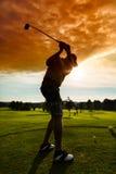 做高尔夫球摇摆的路线的年轻高尔夫球运动员 库存照片