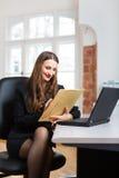 妇女在办公室坐计算机 免版税库存照片