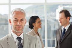 站立在同事前面的商人一起讲话 免版税图库摄影
