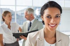在工作的同事前面的快乐的女实业家后边 免版税库存图片