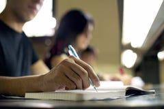 做家庭作业和学习在大学图书馆里的年轻人 免版税库存图片