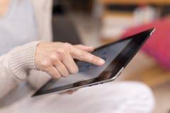 在数字式片剂的妇女手触摸屏。 免版税库存图片