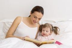 读与她的母亲的孩子一本书 免版税库存照片