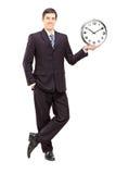 一个年轻人的全长画象拿着时钟的衣服的 库存照片