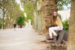 女孩坐一条长凳在公园 免版税图库摄影