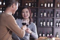 敬酒和开心的微笑的成熟夫妇饮用的酒,在女性的焦点 库存图片