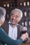 敬酒和开心的微笑的资深夫妇饮用的酒,在男性的焦点 免版税库存照片
