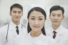 微笑的医疗保健工作者在中国,两位医生和护士画象在医院,看照相机 免版税库存图片