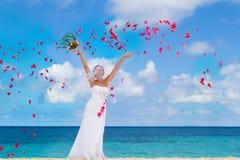 在婚礼之日的愉快的微笑的新娘在热带的海滩 图库摄影