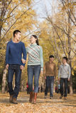 一起走在公园的朋友在秋天 免版税库存图片