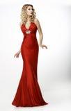 高档时尚。丝绸晚上红色褂子的匀称金发碧眼的女人。阴物 库存照片