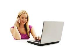 谈话在手机和使用膝上型计算机的妇女 免版税库存图片