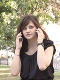 女孩发表演讲关于两个手机 免版税库存图片