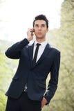年轻商人谈话在电话在办公室外 免版税库存照片