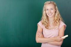 反对黑板的愉快的女学生 免版税库存图片