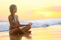 放松-思考在海滩日落的瑜伽妇女 库存图片