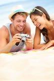 在看照相机的海滩的愉快的夫妇乐趣 免版税库存照片