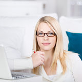 少妇坐有膝上型计算机的沙发 免版税库存图片