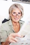 读报纸的退休的妇女 免版税库存照片