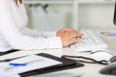 键入在键盘的女实业家在书桌 免版税库存照片
