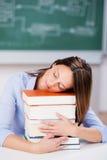 Учитель спать на стоге книг на столе Стоковая Фотография