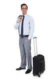 站立在他的行李旁边的微笑的商人 库存图片