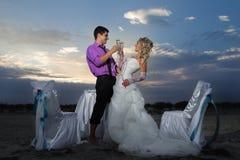 做在日落的新娘和新郎 免版税库存图片