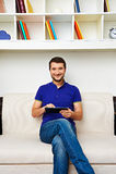 Человек сидя на софе Стоковое Изображение