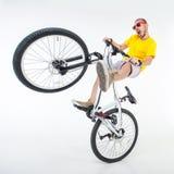 在白色隔绝的土跃迁自行车的疯狂的男孩 免版税库存图片