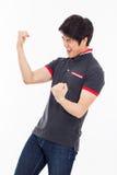 Молодой азиатский человек показывая кулак и счастливый знак. Стоковая Фотография