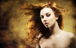 有飞行头发的性感的妇女在难看的东西背景 库存照片