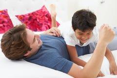 一起使用在床上的父亲和儿子 免版税库存照片