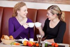 敬酒咖啡杯的朋友在咖啡馆表上 图库摄影