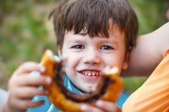 愉快的学龄前男孩提供的可可粉蜗牛 库存图片