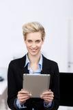 拿着数字式片剂的女实业家在办公室 免版税图库摄影