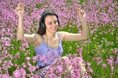 听到与耳机的音乐的美丽的可爱的深色的女孩在华美的草甸 图库摄影