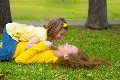演奏说谎在公园草坪的女儿和母亲 免版税库存照片