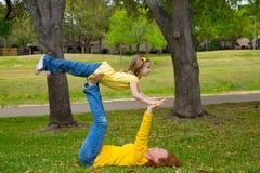 女儿和母亲使用保持平衡说谎在公园 免版税库存照片