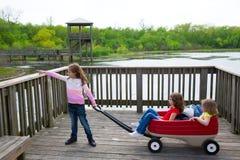 看有室外转储推车的女孩公园湖 免版税库存照片