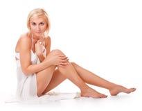 妇女坐地板,显示她亭亭玉立的腿 免版税库存照片