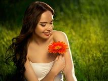 有红色花的美丽的女孩。美丽的式样妇女面孔。 免版税库存照片
