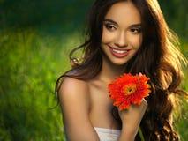 有红色花的美丽的女孩。美丽的式样妇女面孔。 免版税图库摄影