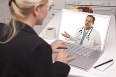 妇女在使用膝上型计算机的厨房里-在网上与护士或医生 免版税库存照片