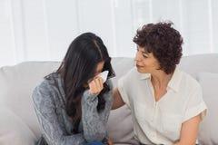 哭泣在她的治疗师旁边的患者 免版税库存图片