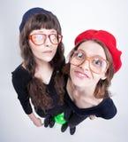 戴老婆婆的眼镜的两个逗人喜爱的女孩做滑稽的面孔 库存图片