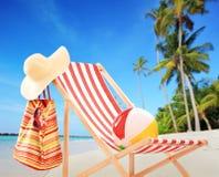 与辅助部件的海滩睡椅在与棕榈的一个热带海滩 免版税库存照片