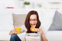 吃新月形面包的妇女 库存照片
